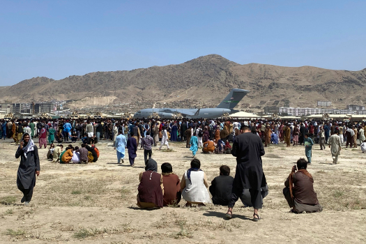 Hundreds of people gather near a U.S. Air Force C-17 transport plane at a perimeter at the international airport in Kabul, Afghanistan, Monday, Aug. 16, 2021. On Monday, the U.S. military and officials focus was on KabulÕs airport, where thousands of Afghans trapped by the sudden Taliban takeover rushed the tarmac and clung to U.S. military planes deployed to fly out staffers of the U.S. Embassy, which shut down Sunday, and others. (AP Photo/Shekib Rahmani)